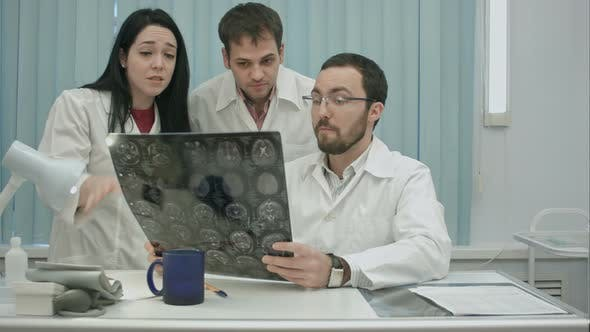 Thumbnail for Trio of Young Afraid Physicians Checking Patient's Head Scanning