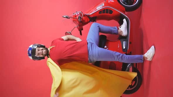 Happy Caucasian Man in a Superhero Helmet and Raincoat Stands Next To a Scooter, Motorcycle