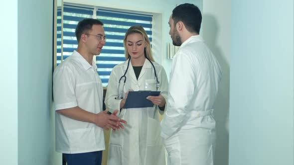 Thumbnail for Two Male Doctors Having Discussion While Female Nurse Making Notes
