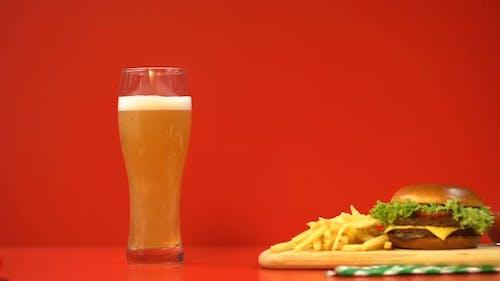 Bierschaum und Hamburger auf rotem Hintergrund, Kohlenhydrate und fetthaltige Lebensmittel