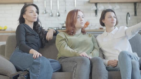 Thumbnail for Relaxed Caucasian Women Sitting on Couch Watching TV and Talking