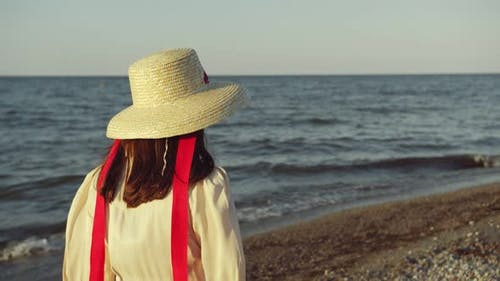 Girl in a Hat Walks Along a Beautiful Beach