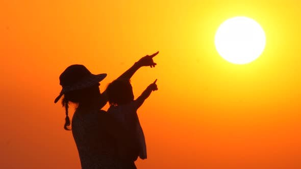 Cover Image for Mother in Hat with Child Looking and Pointing at the Sunset. Baby on Mothers Hands on Orange Sky