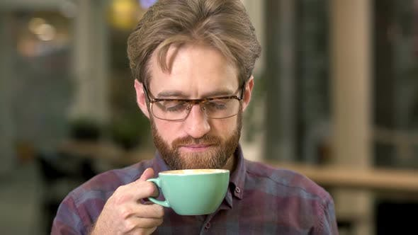 Cover Image for Portrait of Joyful Bearded Man in Glasses Drinking Coffee Close Up. Beardie Clos Eyes Enjoys His