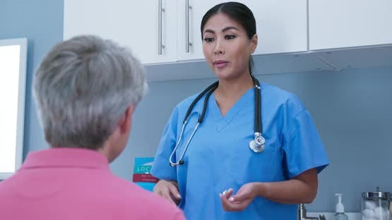 Female surgeon going over recovery steps with senior Caucasian male patient