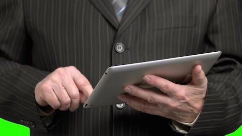 Mann im Anzug Scrolling-Tablet, Nahaufnahme.