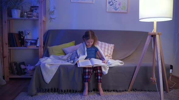 Thumbnail for Girl Child Reads Book In Room On Sofa