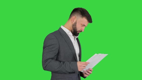 Thumbnail for Turk Businessman Standing and Looking at Documents on a Green Screen, Chroma Key.
