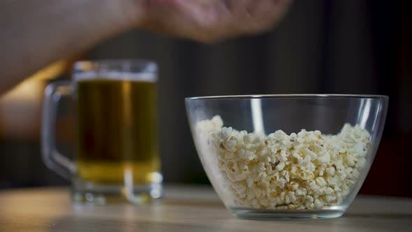 Cover Image for Mans Hand Taking Popcorn from The Bowl, Male Drinking Beer and Watching Movie