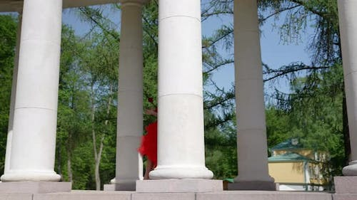 a Blonde with Big Breasts in a Red Fluffy Dress and with a Rose is Walking Through the Columns