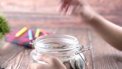 Child Girl Holding Jar of Coins Close Up