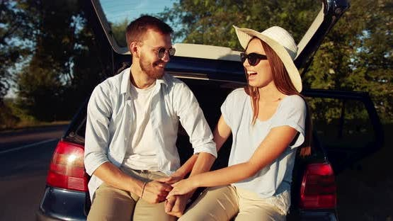 Couple Sitting in Car Trunk on Sunset