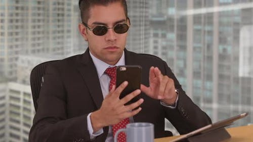Businessman using cell phone while working in office with city view