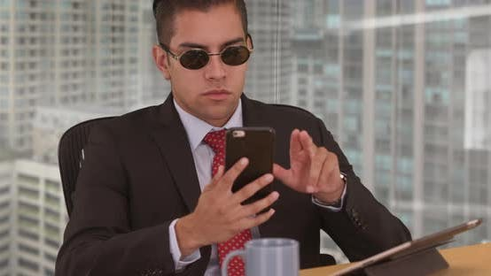 Thumbnail for Businessman using cell phone while working in office with city view