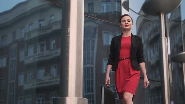 Thumbnail for Self-confident Business Woman in a Red Dress Walks Against the Backdrop of Modern Buildings