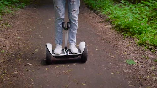 A Girl Dressed in Casual Rides Through the Forest on a Gyro Scooter