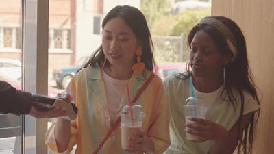 Asian Woman Paying by Credit Card in Cafe