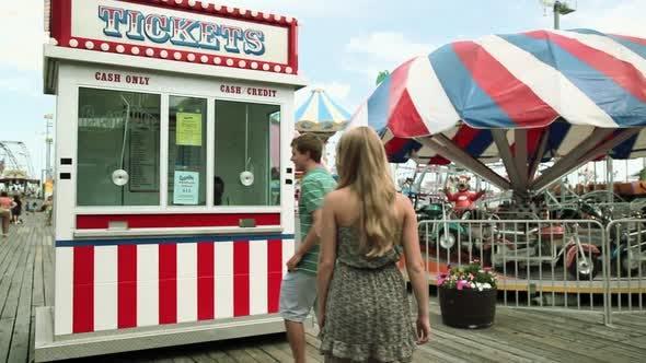Thumbnail for Teenage girl taking boyfriend to ticket booth in fun fair