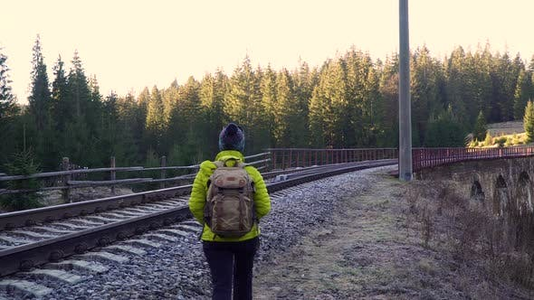 Thumbnail for A Woman with a Backpack Walks on the Railway