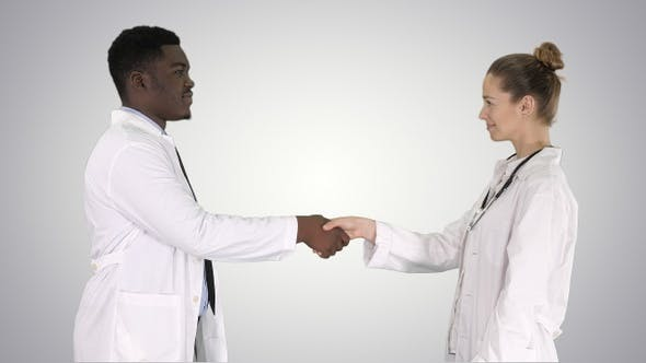 Thumbnail for Two young doctor shaking hands on gradient background.