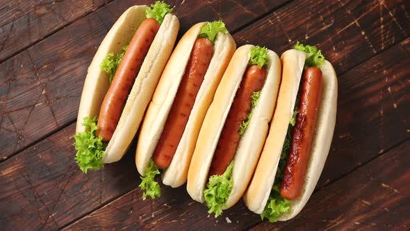 Thumbnail for Tasty American Hot Dogs Assorted in Row. Placed on Wooden Table