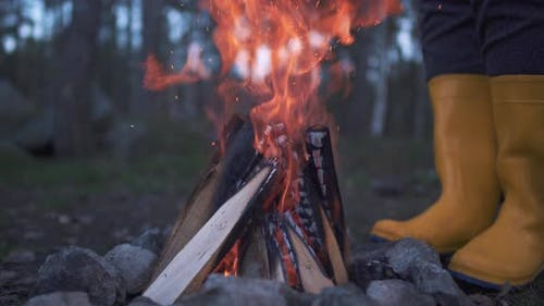 Human Legs in Yellow Rubber Boots Standing Near a Burning Fire in the Forest