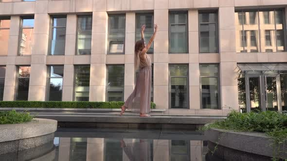 Thumbnail for Beautiful Young Girl Dancing on the Street of a Modern City and Is Reflected in the Water. Slow