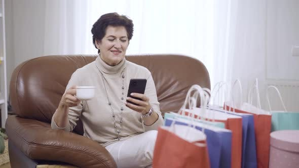 Thumbnail for Portrait of Carefree Stylish Woman Drinking Tea or Coffee at Home After Shopping and Messaging
