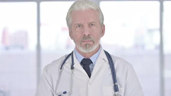 Portrait of Old Senior Doctor Looking at the Camera