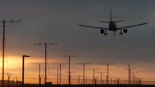 Airplane Landing in LAX Airport at Sunset, Los Angeles, California USA. Passenger Flight or Cargo