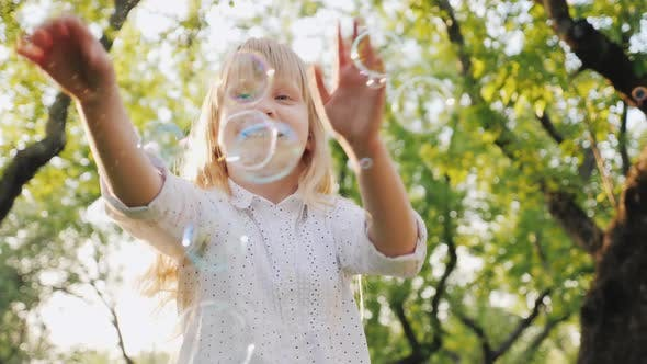 Cover Image for A Cheerful Blonde Girl Is Playing with Soap Bubbles. Carefree Happy Childhood Concept