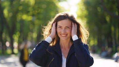 Happy Woman Walking in Park in Bright Sunshine