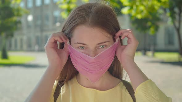 Thumbnail for Close-up Portrait of Charming Young Woman Taking Off Face Mask and Smiling at Camera. Beautiful