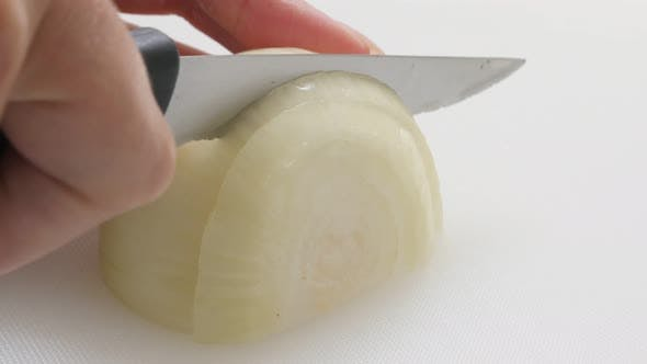 Thumbnail for Organic common bulb onion chopping up with knife on white board 4K 2160p 30fps UHD footage - White A