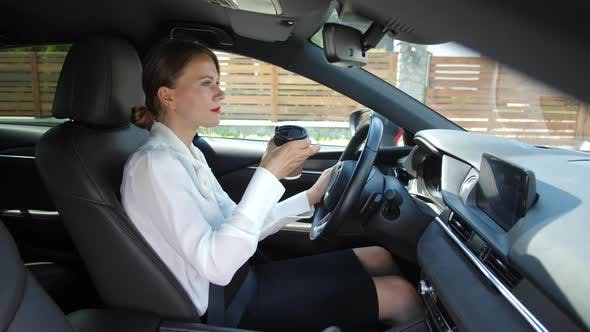 Thumbnail for Businesswoman Drinking Coffee While Driving Car