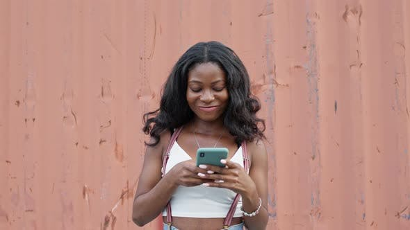 Thumbnail for Cheerful Pretty Girl. Young Black Girl With Mobile Phone In Her Hands.