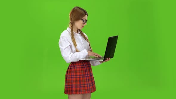 Thumbnail for Student Holds a Laptop in Her Hands and Prints on the Keys. Green Screen
