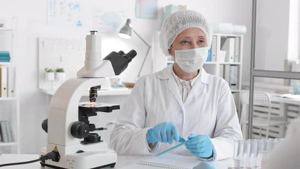 Laboratory Worker Looking through Microscope