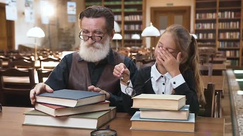Tired Respected Man with Beard and His Blond Pretty Granddaughter Resting on the Books