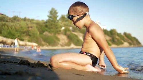 Child sitting on the sand and enjoying sea waves washing him