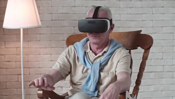 Thumbnail for Elderly Man in VR Goggles Touching Air