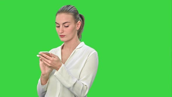 Cover Image for Pensive Business Woman Using Mobile Cell Phone Reading Message, Wear White Suit on a Green Screen