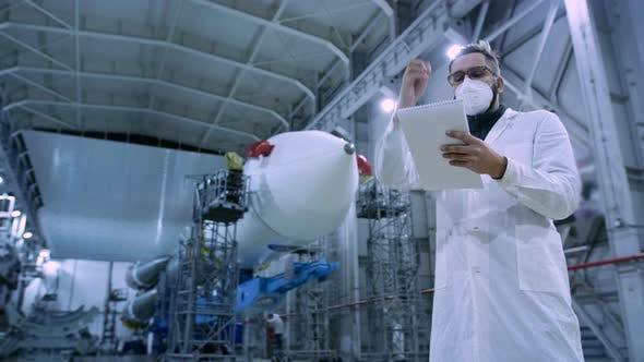 Adult Engineer of Industry Four in Face Mask Working in Large Space Production