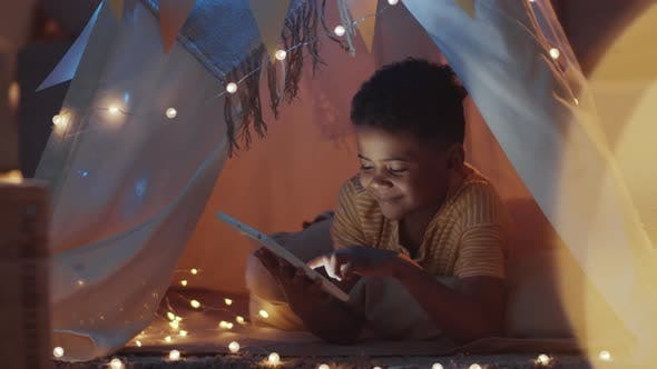 Smiling Afro-American Boy Using Tablet in Cozy Teepee in Dark Room