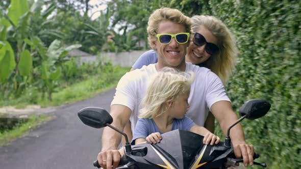 Thumbnail for Carefree Family Riding on Scooter in Tropics
