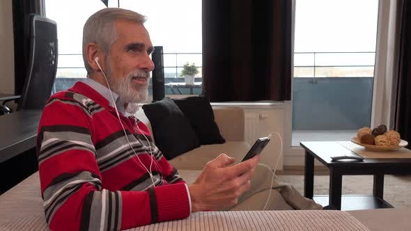 Thumbnail for A Happy Elderly Man Sits on a Couch in Apartment and Listens To Music on a Smartphone with a Smile