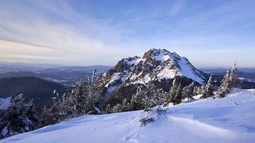 Last rays on snowy mountain with colorful sky, golden hour,