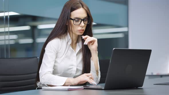 Businesswoman Browsing Internet and Making Notes