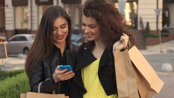 Thumbnail for Girl Shows Her Friend Something on Her Smartphone on the Street of the City