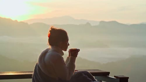 Young Woman is Sitting with a Mug of Coffee on a Cliff Overlooking the Mountains with Fog